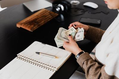 crop-entrepreneur-counting-money-in-office-4475527