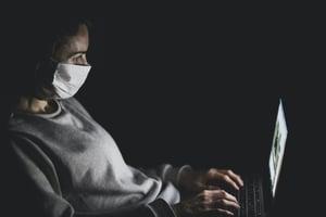 woman-wearing-face-mask-using-black-laptop-computer-4031905